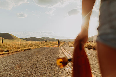 Young male skateboarder skateboarding on rural road, girlfriend watching, Exeter, California, USA - p924m2098159 by Peter Amend