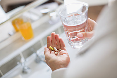 Woman taking vitamins and glass of water - p1023m1577434 by Sam Edwards