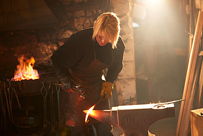 Female blacksmith forging steel in workshop - p1023m2200938 by Himalayan Pics