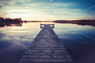 Pier on a lake at sunset - p1690m2281242 by Marie Carr