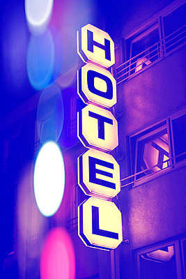 Germany, Duesseldorf, facade of hotel with lighted sign at night - p300m1019069f by Fotomaschinist