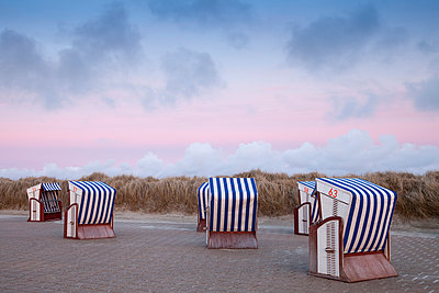 Germany, Lower Saxony, East Frisia, Nordstrand, beach with roofed wicker beach chairs, afterglow - p300m1153695 by Wilfried Wirth