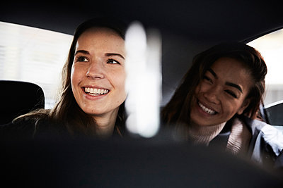 Smiling young female friends looking away while sitting in taxi - p426m1518090 by Maskot
