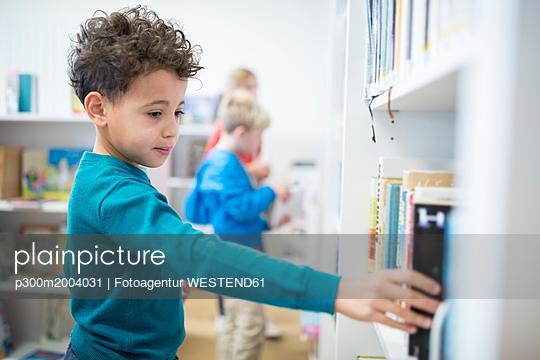 Schoolboy taking book from shelf in school library - p300m2004031 von Fotoagentur WESTEND61