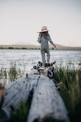 Rear view of girl walking on driftwood at lakeshore against clear sky - p1166m1489787 by Cavan Images