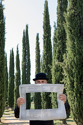 Italy, Tuscany, invisible man surrounded by cypresses reading newspaper with a hole - p300m2104375 by Petra Stockhausen