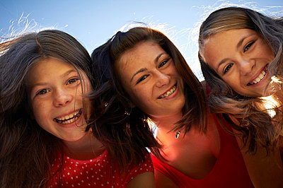 Girls smiling against blue sky - p42916560f by Adrian Weinbrecht