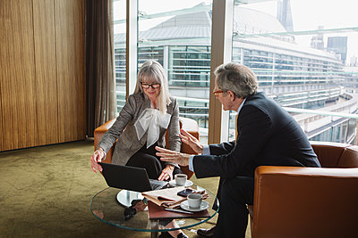 Businessman and businesswoman in coffee area in office, London, UK - p429m1448179 by Nancy Honey