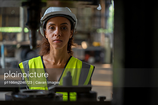 Factory female worker working and checking with clipboard in han - p1166m2246723 by Cavan Images