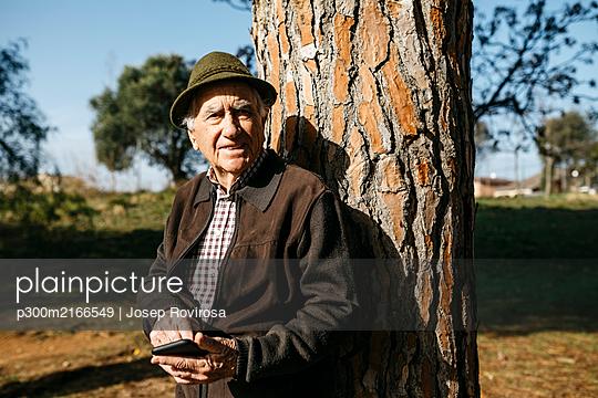 Old man using smartphone, leaning on tree trunk - p300m2166549 by Josep Rovirosa