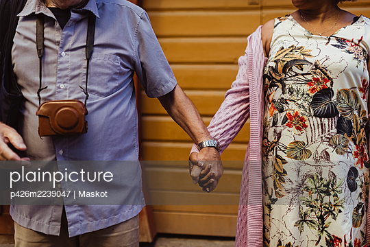 Midsection of senior couple holding hands against wall - p426m2239047 by Maskot