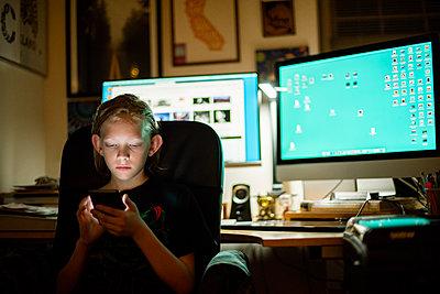 Kid sitting at desk using smart phone - p1166m2131145 by Cavan Images
