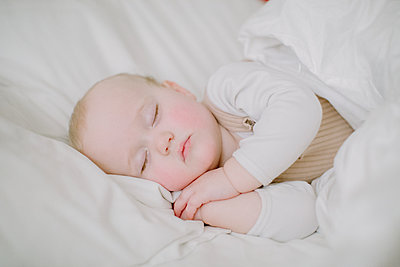 Baby girl sleeping peacefully in white bed facing camera with hands fo - p1166m2191803 by Cavan Images