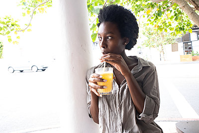 Young African woman has a soft drink - p1640m2260100 by Holly & John