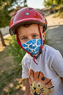 Close-up of boy wearing mask and red helmet standing outdoors - p300m2203172 by Veam