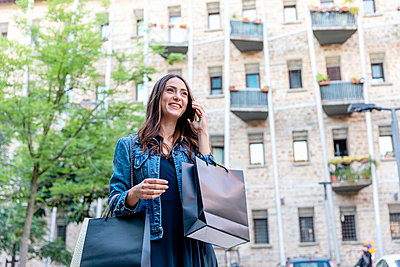 Smiling woman with shopping bags talking on mobile phone in city - p300m2287530 by Emma Innocenti