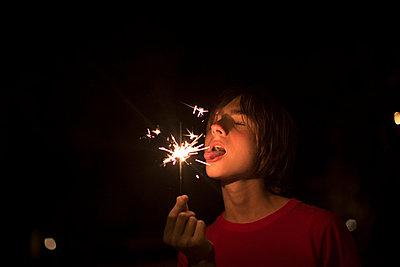 Portrait of boy holding sparkler on independence day; Destin; Florida; USA - p429m859923 by Raphye Alexius