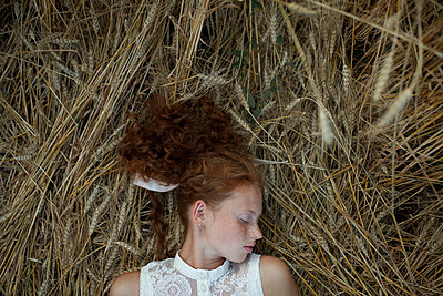 Serious Caucasian girl with freckles laying in wheat - p555m1521372 by Vyacheslav Chistyakov