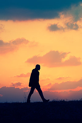 Man silhouette walking on field at sunset  - p794m2073040 by Mohamad Itani