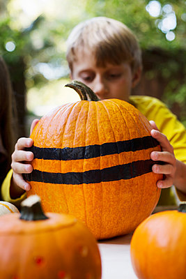 Boy lifting large stripe painted pumpkin from garden table - p924m1469128 by Kinzie Riehm