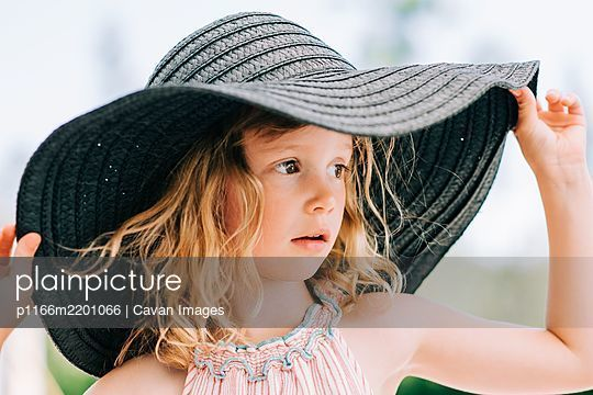 candid close up portrait of a young girl stood outside with a sun hat - p1166m2201066 by Cavan Images