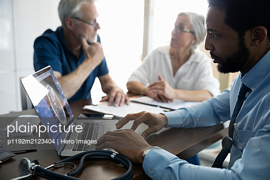 Medical consultant using laptop with senior couple - p1192m2123404 by Hero Images
