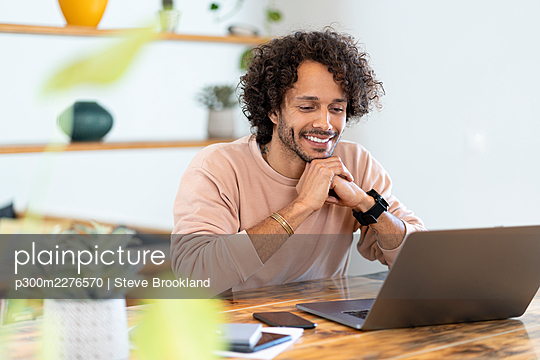 Smiling man with hands clasped looking at laptop on table at home - p300m2276570 by Steve Brookland