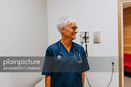 Smiling doctor looking away - p312m2237217 by Plattform