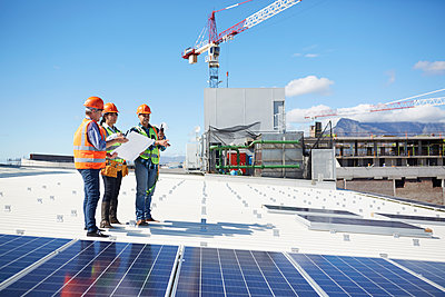 Engineers with blueprint at solar panels at sunny power plant - p1023m1583992 by Trevor Adeline