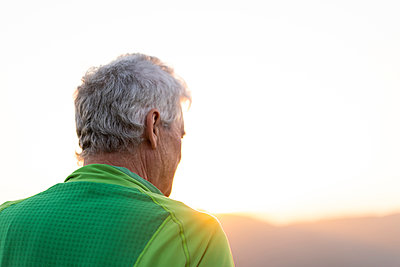 Rear view of senior man on top of hill looking the sunset - p1166m2094247 by Cavan Images