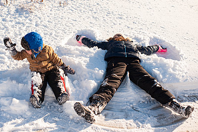 Brother and Sister playing in the snow in front yard - p1166m2136750 by Cavan Images