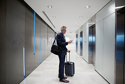 Businessman with luggage texting waiting for elevator in airport corridor - p1192m1183770 by Hero Images