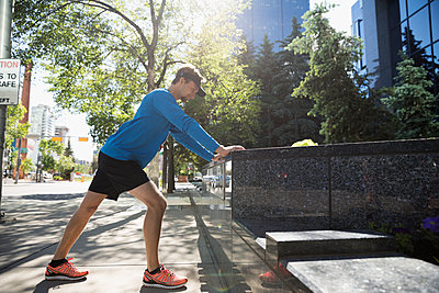Young male runner stretching leg hamstrings on sunny urban sidewalk - p1192m1490347 by Hero Images