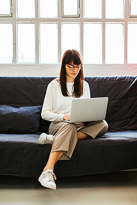 Young woman sitting on couch in office using laptop - p300m1587287 by Bonninstudio
