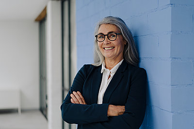 Portrait of smiling grey-haired businesswoman standing at a blue wall - p300m2170196 by Gustafsson