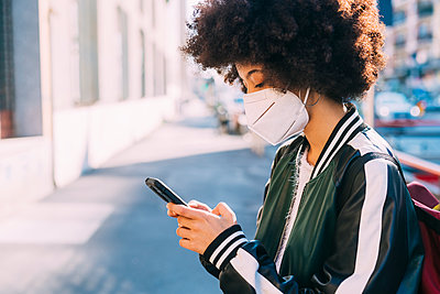 Woman wearing protective face mask using smart phone - p300m2286234 by Eugenio Marongiu