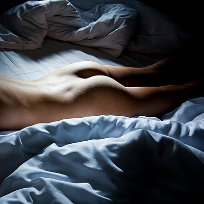 Woman lying naked on a bed - p4130731 by Tuomas Marttila