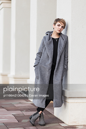 Stylish woman with short haircut in gray coat on white background - p1166m2130425 by Cavan Images