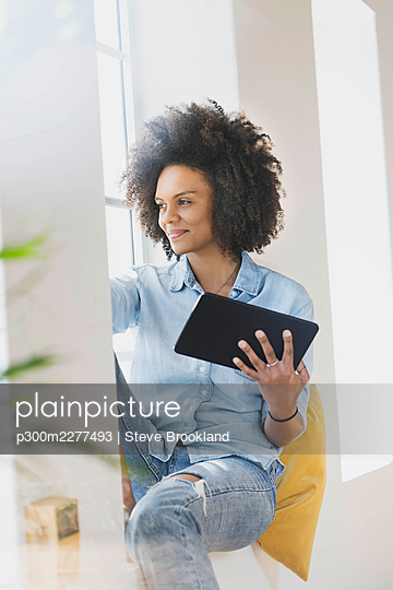 Young woman with digital tablet sitting at window - p300m2277493 by Steve Brookland