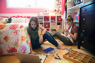 Girls making jewelry in bedroom - p1192m1158033 by Hero Images