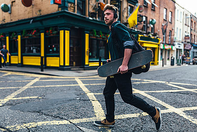 Ireland, Dublin, young man with headphones and skateboard crossing the street - p300m1189501 by Boy photography