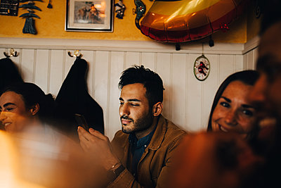 Young man using mobile phone while sitting amidst friends at restaurant - p426m2046292 by Maskot