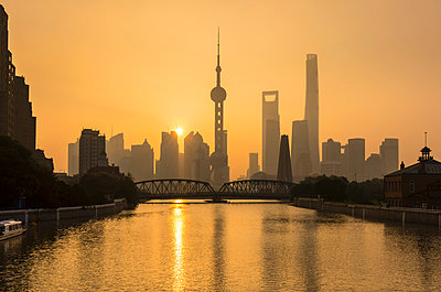 Golden sunset over Waibaidu Bridge and Pudong skyline, Shanghai, China - p429m2074997 by Henglein and Steets