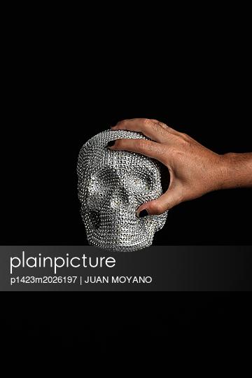 Hand holding skull with diamonds  - p1423m2026197 by JUAN MOYANO