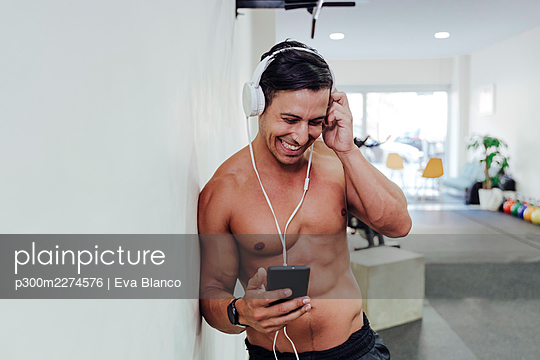 Male athlete adjusting headphone while using mobile phone in gym - p300m2274576 by Eva Blanco