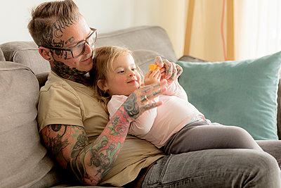 Kleines Mädchen liegt mit Vater auf dem Sofa - p1212m1440495 von harry + lidy