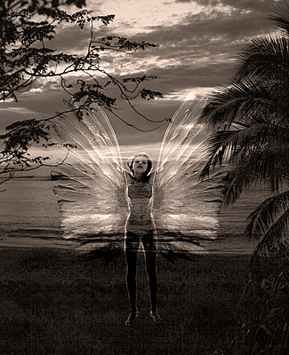 Girl with Wings on Beach at Night - p1636m2216327 by Raina Anderson