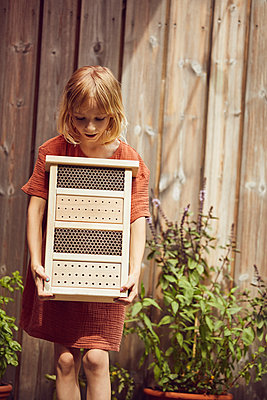 Girl carrying insect hotel while standing against house in yard - p300m2214204 by Maya Claussen