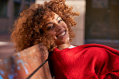 Young woman smiling while leaning on bench - p300m2257353 by Veam
