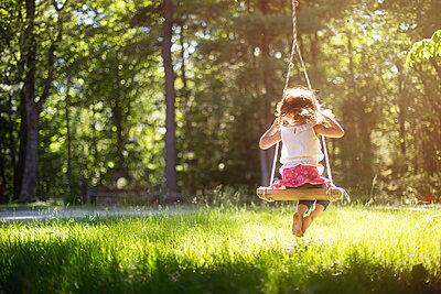 Girl sitting on swing in field - p555m1409496 by Shestock